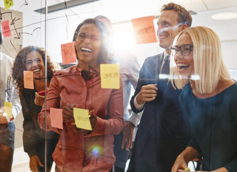 Laughing group of diverse businesspeople having a brainstorming session together with sticky notes in an office